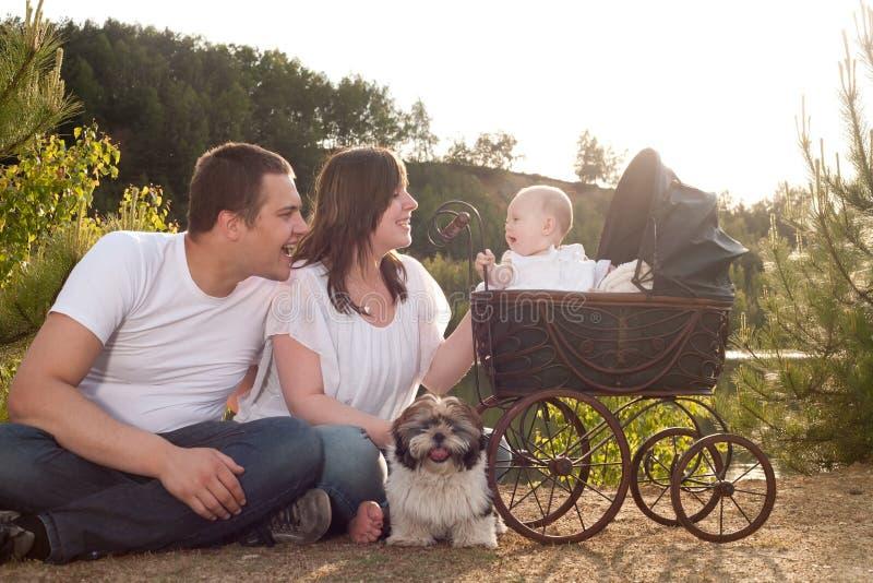 与葡萄酒摇篮车的愉快的家庭 免版税库存照片