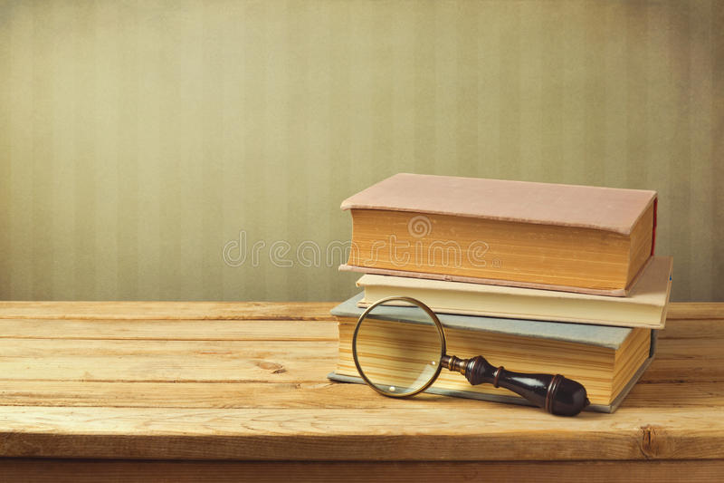与葡萄酒放大镜的旧书 库存图片