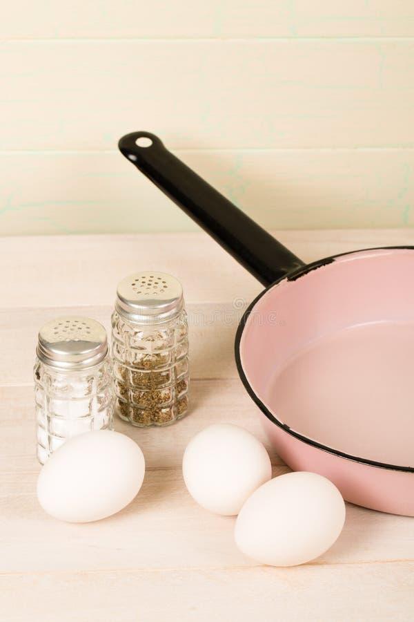 与葡萄酒桃红色煎锅的鸡蛋 库存图片