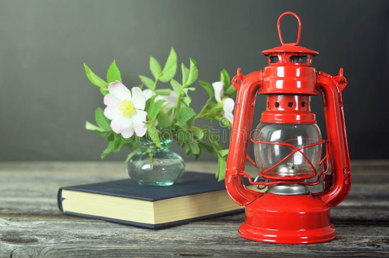 与葡萄酒油灯、书和狗的静物画上升了在花瓶的花在木背景 免版税库存照片