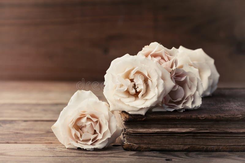 与葡萄酒玫瑰色花和古老书的减速火箭的静物画 在老木桌上的怀乡构成 库存图片