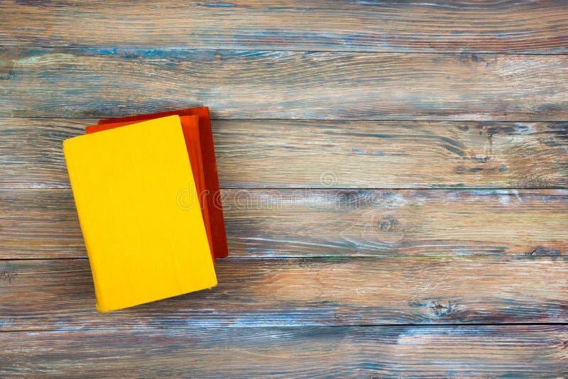 与葡萄酒老精装书的构成预定,在难看的东西木甲板桌背景的日志 回到学校 复制空间 免版税库存照片