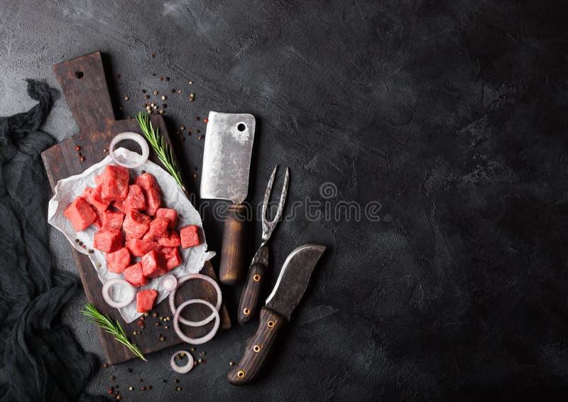 与葡萄酒肉柴刀的未加工的精瘦的切成小方块的砂锅牛肉猪肉与刀子的牛排和叉子在石背景 有红色的罗斯玛丽 库存照片