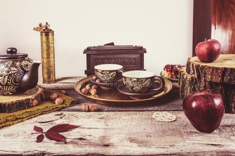 与葡萄酒茶瓦器的老减速火箭的厨房用桌 库存照片