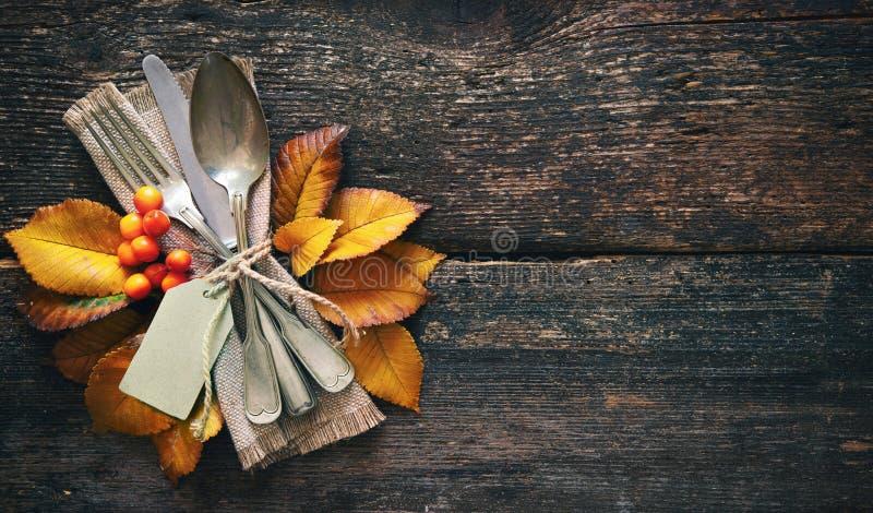 与葡萄酒餐位餐具的秋天背景在老木桌上 免版税库存图片