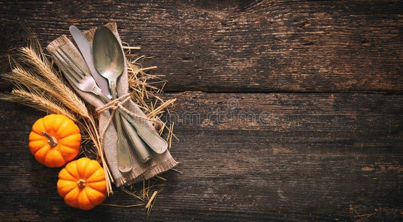与葡萄酒餐位餐具的秋天背景在老木桌上 免版税库存照片