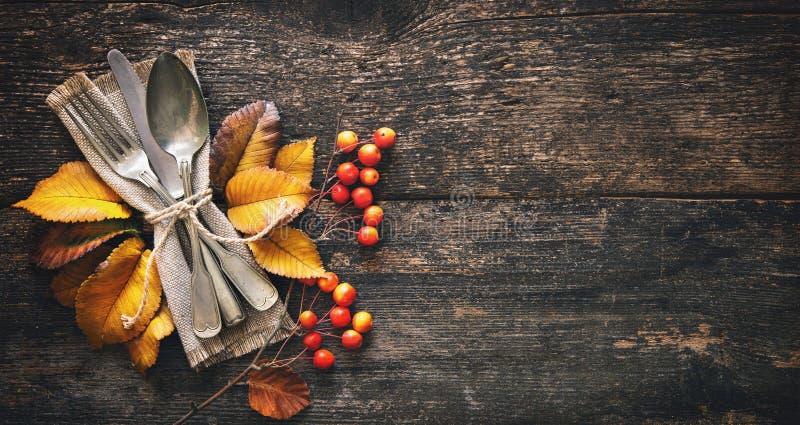 与葡萄酒餐位餐具的秋天背景在老木桌上 库存图片