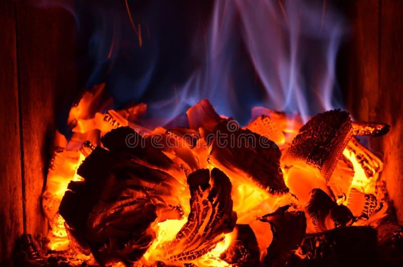 与蓝焰的明亮的橙色炭烬在木火炉 免版税库存图片