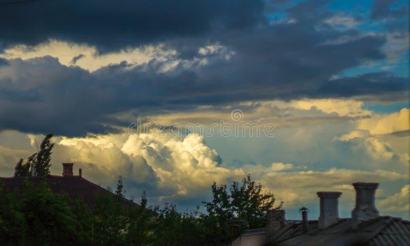 与蓝色云彩的黄色日落在屋顶上 免版税库存图片