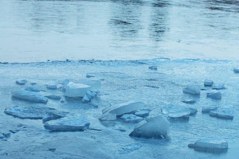 与蓝色冰大块的冻结的湖表面  免版税库存照片