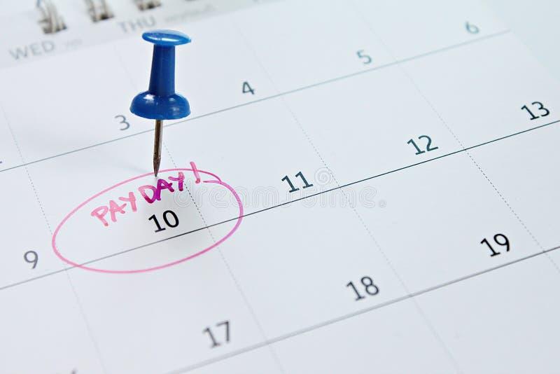与蓝色图钉的日历在词发薪日为提醒 免版税库存图片