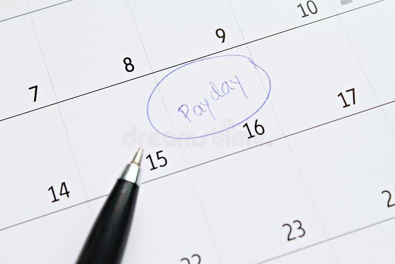 与蓝色圆识别标的日历在词发薪日为提醒 库存图片