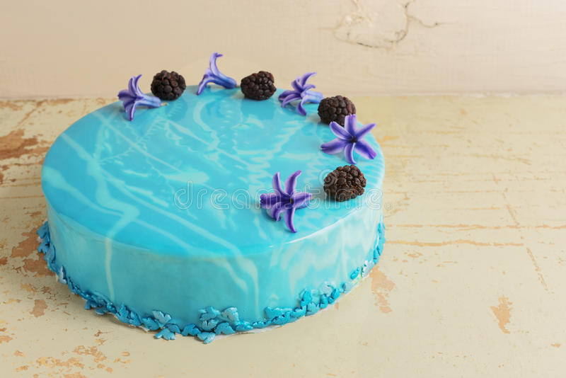 与蓝色大理石镜子釉的现代时髦奶油甜点蛋糕 花和黑莓装饰 免版税图库摄影