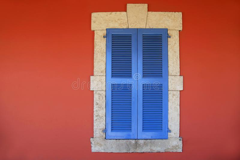 与蓝色快门的窗口在老红色灰泥房子里 免版税库存照片