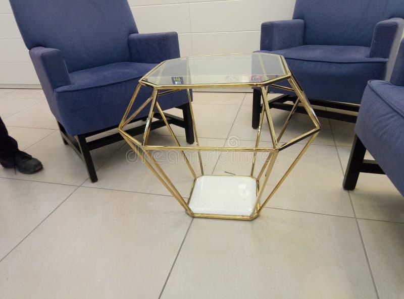 与蓝色扶手椅子的一张金色金刚石桌在它附近 库存照片