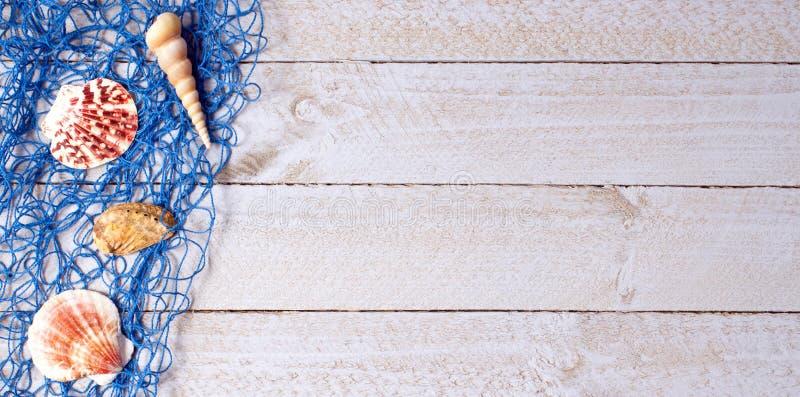 与蓝色捕鱼网的壳在木背景 免版税库存照片