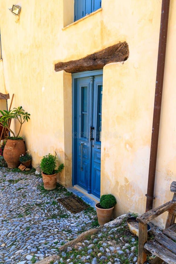 与蓝色木门的典型的希腊,地中海房子入口 克利特,希腊 免版税库存图片