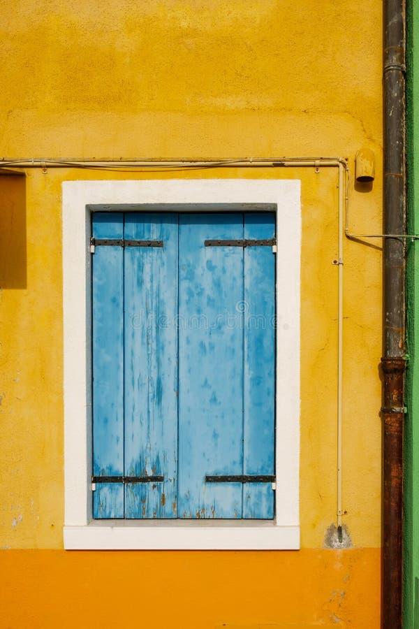 与蓝色木闭合的窗帘的老窗口在破旧的黄色墙壁上 免版税图库摄影