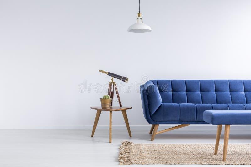 与蓝色沙发的明亮的公寓 库存照片