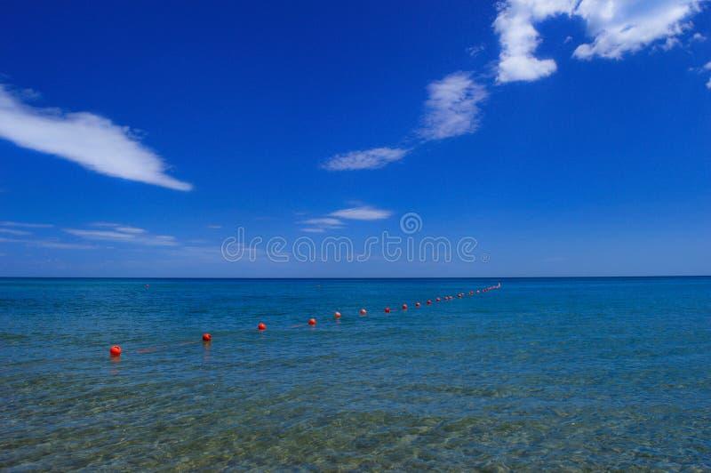 与蓝色海和红色风向指示标的蓝天 免版税库存照片