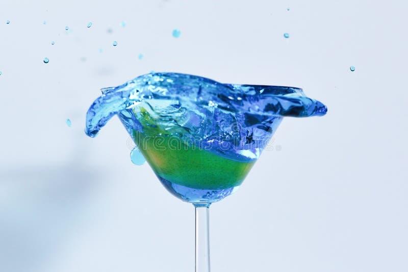 与蓝色液体的鸡尾酒在玻璃 与倾吐与液体的大海的玻璃与飞溅并且落下 填装与的马蒂尼鸡尾酒玻璃 免版税图库摄影