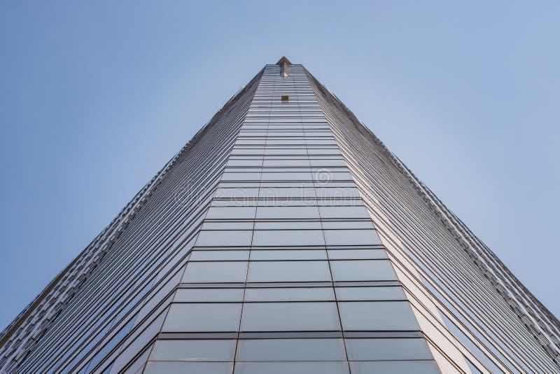 与蓝色玻璃窗的高楼在曼谷、泰国、看法和透视从地面,上面天空蔚蓝 免版税库存图片