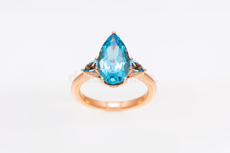 与蓝色珍贵的宝石的钻戒 在轻的背景的黄色金黄圆环 时尚豪华辅助部件 免版税库存照片