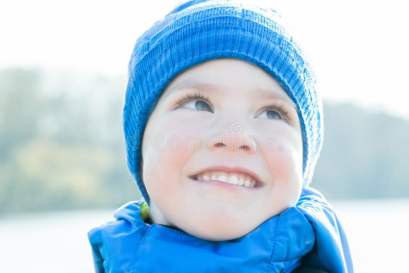 与蓝色的快乐的小男孩特写镜头画象编织了帽子 图库摄影