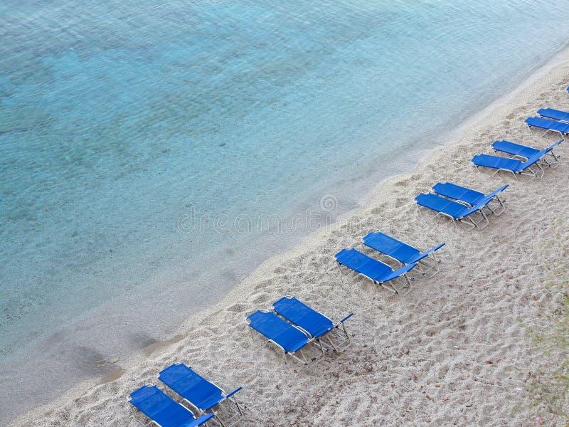 与蓝色空的deckchair的热带沙子海滩 免版税库存图片