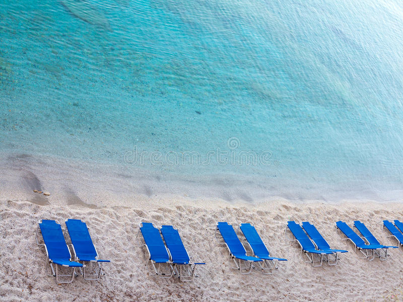 与蓝色空的deckchair的热带沙子海滩 免版税图库摄影