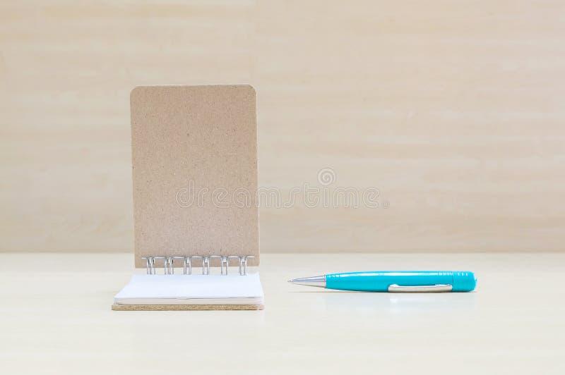 与蓝色笔的特写镜头表面开放笔记本在被弄脏的棕色木书桌和木头墙壁上构造了与拷贝空间的背景在wi下 库存照片