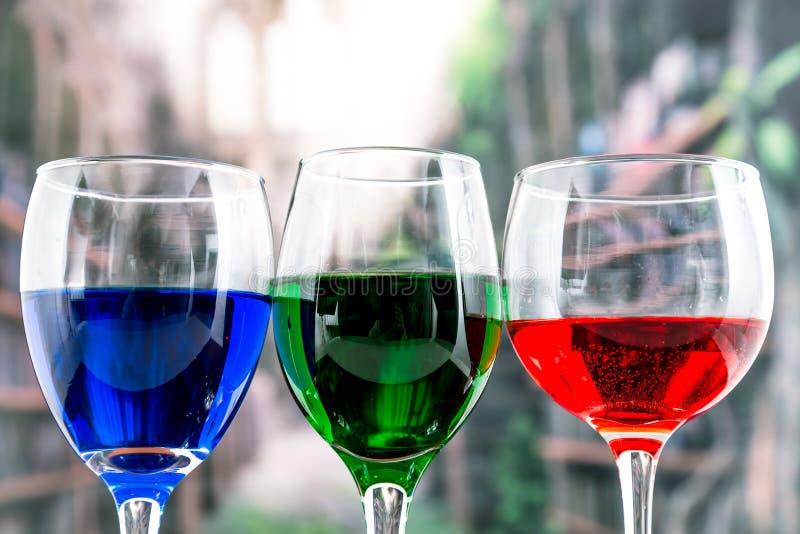 与蓝色红色和绿色液体鸡尾酒的玻璃 免版税图库摄影