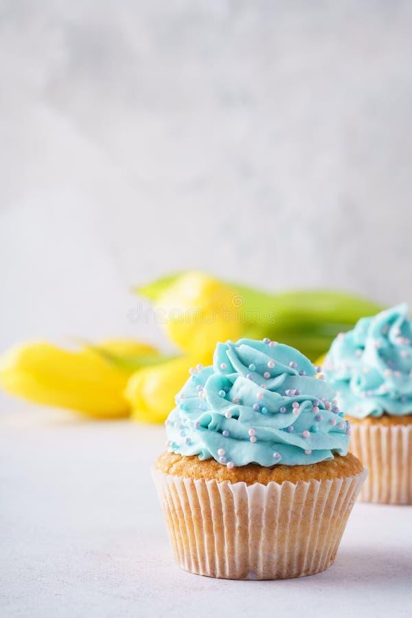 与蓝色结霜和黄色花的香草杯形蛋糕 免版税库存照片