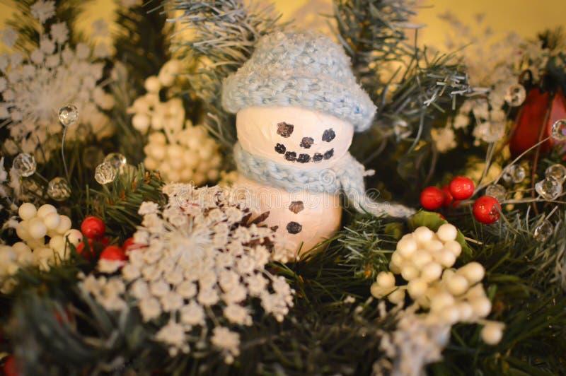 与蓝色编织帽子和围巾的雪人装饰品 库存照片