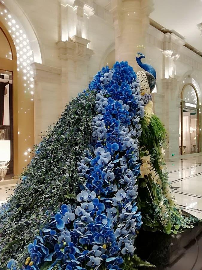 与蓝色花的孔雀 免版税库存图片