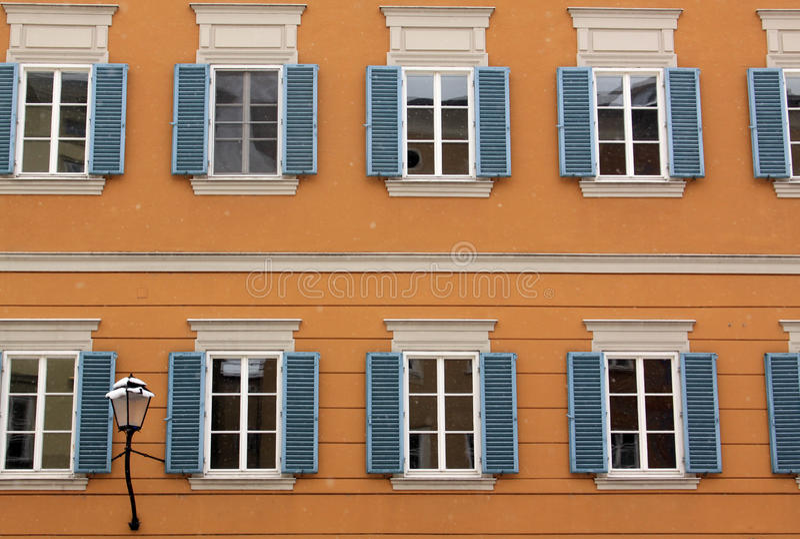 与蓝色被打开的窗口的橙色大厦 免版税库存照片