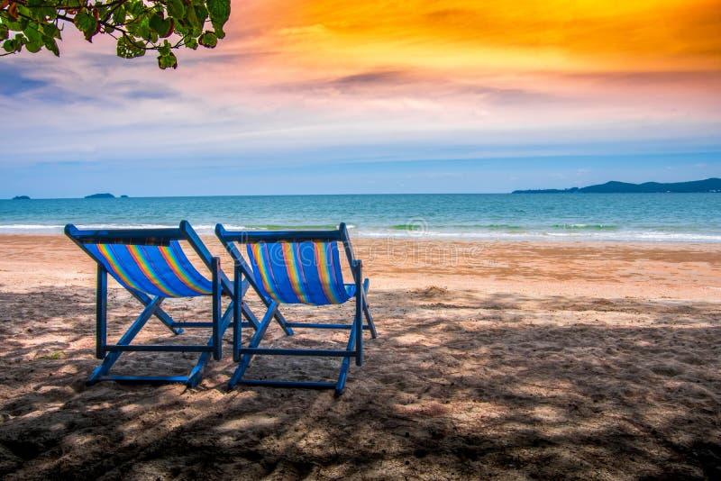 与蓝色颜色的折叠椅在海滩在阳光下有海视图/自然和假日 免版税图库摄影