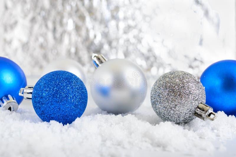 与蓝色,银色和白色圣诞节快乐球的新年横幅在抽象冬天背景的雪 库存照片