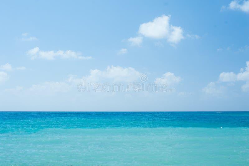 与蓝色晴朗的天空的完善的热带白色沙滩和绿松石清楚的海洋水的暑假自然本底 库存照片