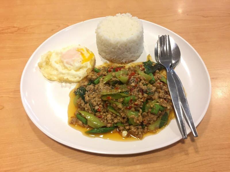 与蓬蒿叶子和煎蛋的油煎的剁碎的猪肉用在白色盘的米与在木桌上的利器 免版税图库摄影