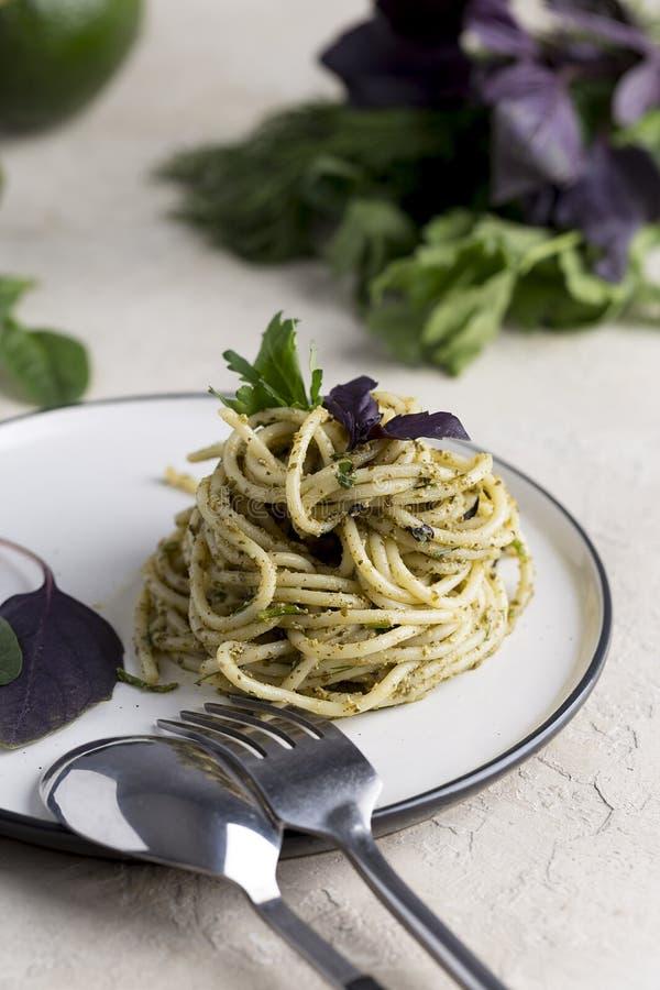 与蓬蒿pesto的意大利面团在轻的背景的白色板材 图库摄影