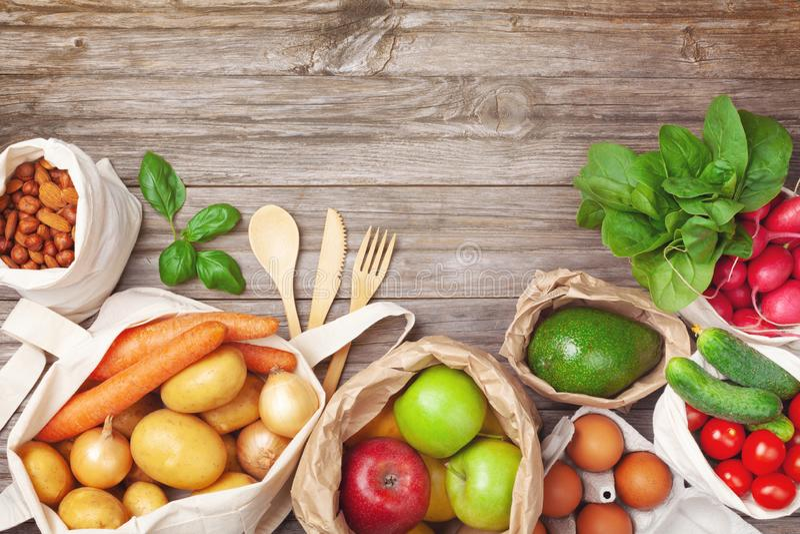 与蔬菜和水果的零的废物和eco友好的购物在自然纺织品和纸袋顶视图 r 库存图片
