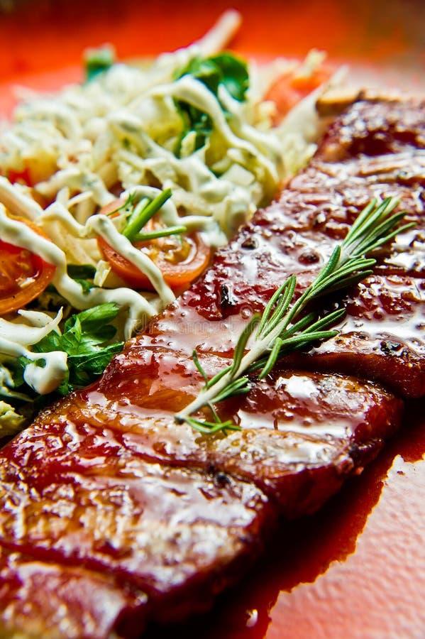 与蔬菜沙拉小菜的传统美国烤肉排骨  灰色背景,侧视图,特写镜头 图库摄影
