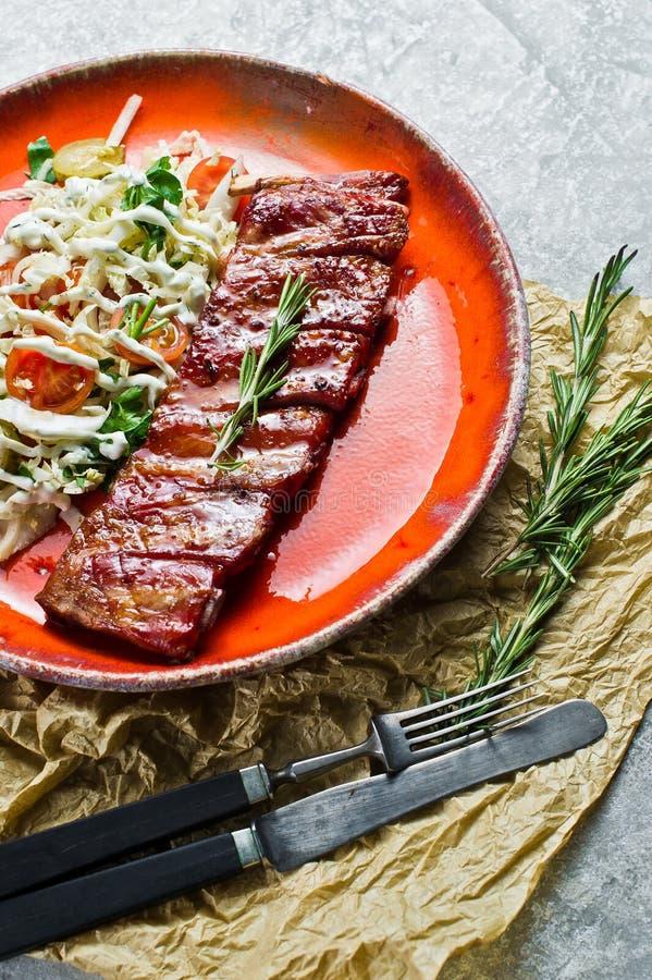 与蔬菜沙拉小菜的传统美国烤肉排骨  灰色背景,侧视图 库存图片