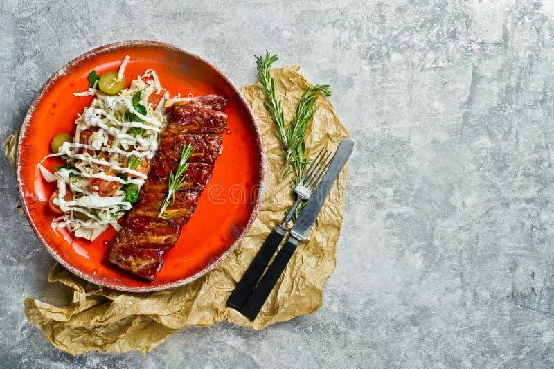 与蔬菜沙拉小菜的烤肉排骨  灰色背景,顶视图,文本的空间 免版税库存照片