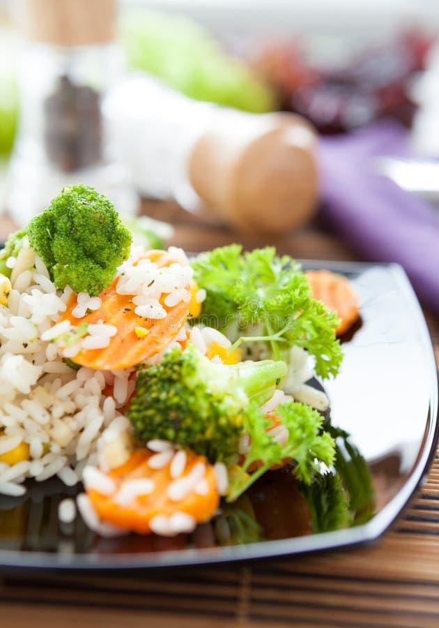 与蔬菜的米在黑色盘 免版税图库摄影