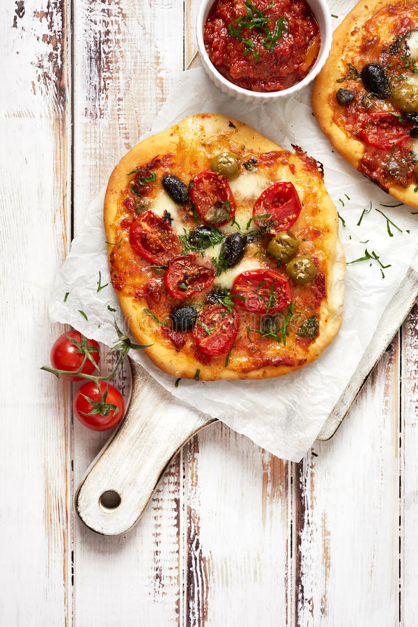 与蕃茄、橄榄和草本的加法的小自创菜薄饼在一张白色木桌上 库存照片