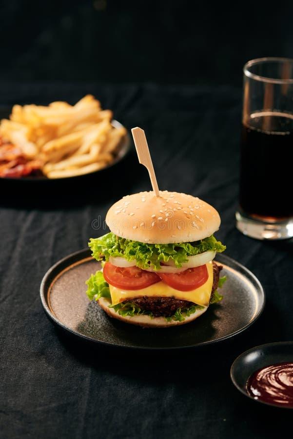 与蕃茄和乳酪和可乐玻璃的可口新鲜的汉堡在背景 快餐概念晚餐 库存照片