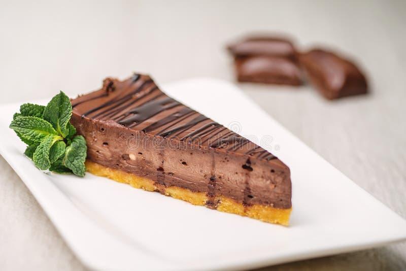 与薄荷的叶子的巧克力或咖啡cheescake在白色板材,面筋自由蛋糕,法式蛋糕铺的产品摄影 免版税图库摄影