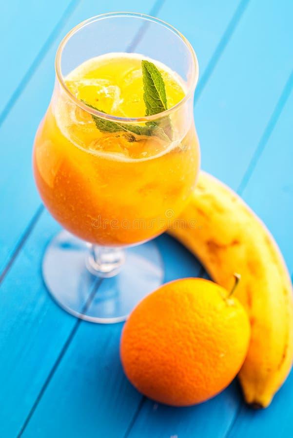 与薄荷的叶子的新鲜的橙色圆滑的人在蓝色木背景、桔子、芒果、红萝卜或者香蕉饮料,产品photogr的玻璃 图库摄影